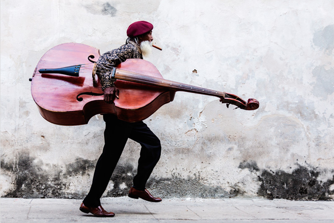 Cuban Man with Large Moustache Walking with Double Bass by Jeremy Woodhouse